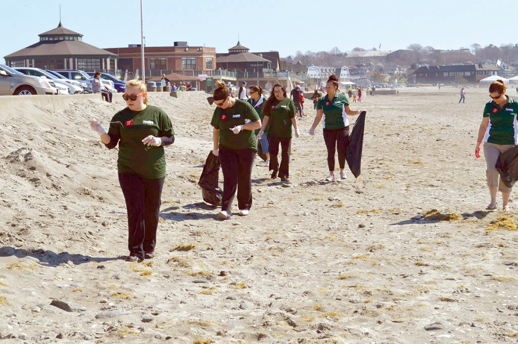 BEACH CLEANUP: Representatives from People's Credit Union assist in a cleanup of Easton's Beach in Newport hosted by Save The Bay. The organization will hold a communitywide Earth Day birthday party at the beach on April 27.