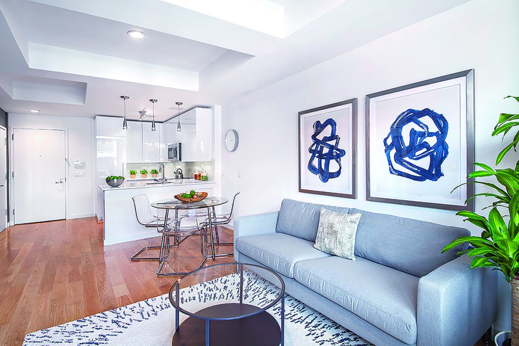 NYC STYLE: Pictured is a photograph of the kitchen and living area interior of The Style, a pair of mid-rise condominium buildings built by The Fane Organization in East Harlem in New York City. The 31-unit project was completed in 2017 and overseen by Daria Fane, vice president of the company. / COURTESY THE FANE ORGANIZATION