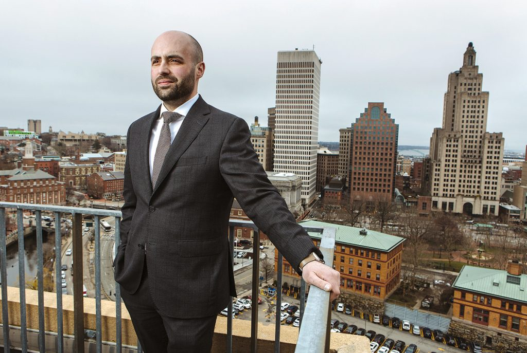 """ROOFTOP VIEW: Benjamin Scungio, the Providence office manager for luxury real estate company Mott & Chace Sotheby's International Realty, shows the view from the rooftop courtyard at Waterplace, which overlooks downtown Providence. The Industrial Trust Building, aka """"the Superman Building,"""" is shown at right. / PBN PHOTO/RUPERT WHITELEY"""