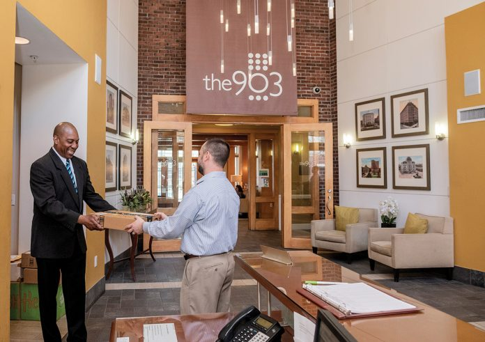 CONDO CONVERSIONS: Tom Knight, left, concierge at the 903 Residences at Providence Place, delivers a package to General Manager Walter Pastor. For the past six months, rental units at the residential building in Providence have been going through a conversion to condos, with nearly 40 sold so far.   / PBN PHOTO/MICHAEL SALERNO