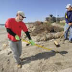 MILITARY VETERANS Matthew Paquette, left, and Jonathan Segal pitched in to help with storm cleanup at Scarborough State Beach in Narragansett in this 2017 photo. / PBN FILE PHOTO/MARTIN GAVIN