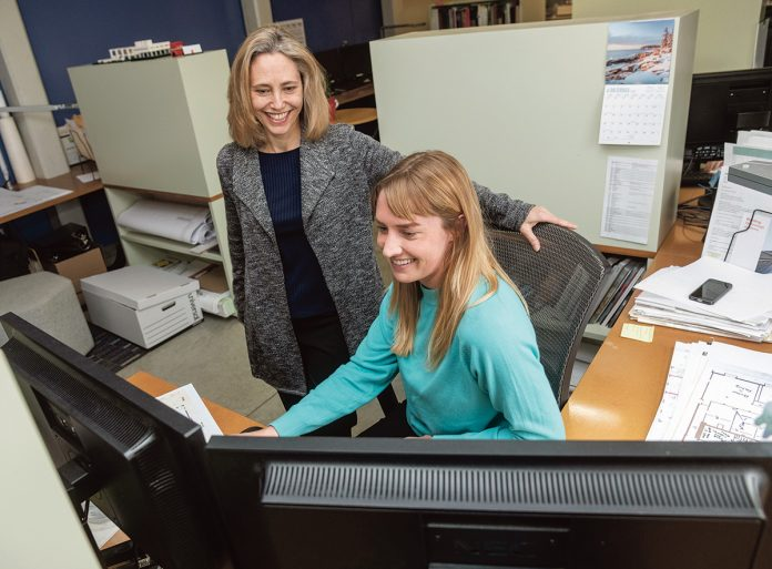 BUILDING HER WAY: Kathleen Bartels, left, principal at LLB Architects in Pawtucket, speaks with Haley Hardwick-Witman, architect. Bartels studied Russian before discovering her love of architecture. / PBN FILE PHOTO/MICHAEL SALERNO