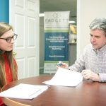 FINANCIAL PLANNING: Jeffrey Kreyssig, owner of Padgett Business Services, meets with client Abbey Dyer, office manager for Narragansett Property Management, in his Narragansett office.