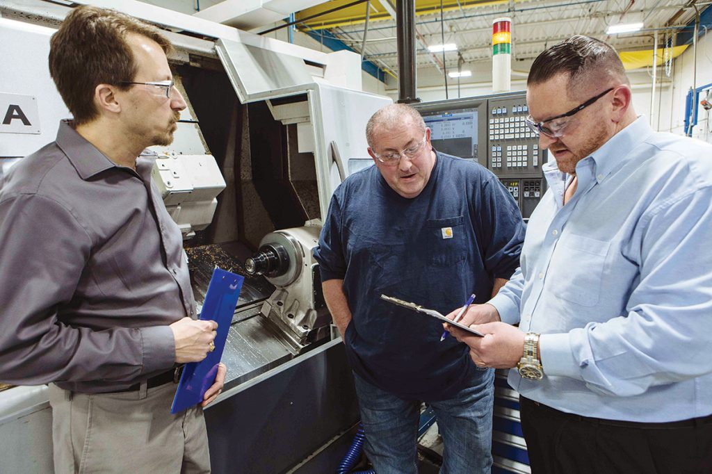 SAFETY CHECKLIST: Plant Manager Craig Danko, left, and Production Manager Joe Cairo, right, review safety checklists with Michael Simpson, a setup machinist, at multinational materials and construction manufacturer Saint-Gobain in Bristol, which has gone about four years without an employee hospitalization. As part of the onboarding process, employees are trained in safety techniques and how to perform a process step by step. / PBN FILE PHOTO/RUPERT WHITELEY