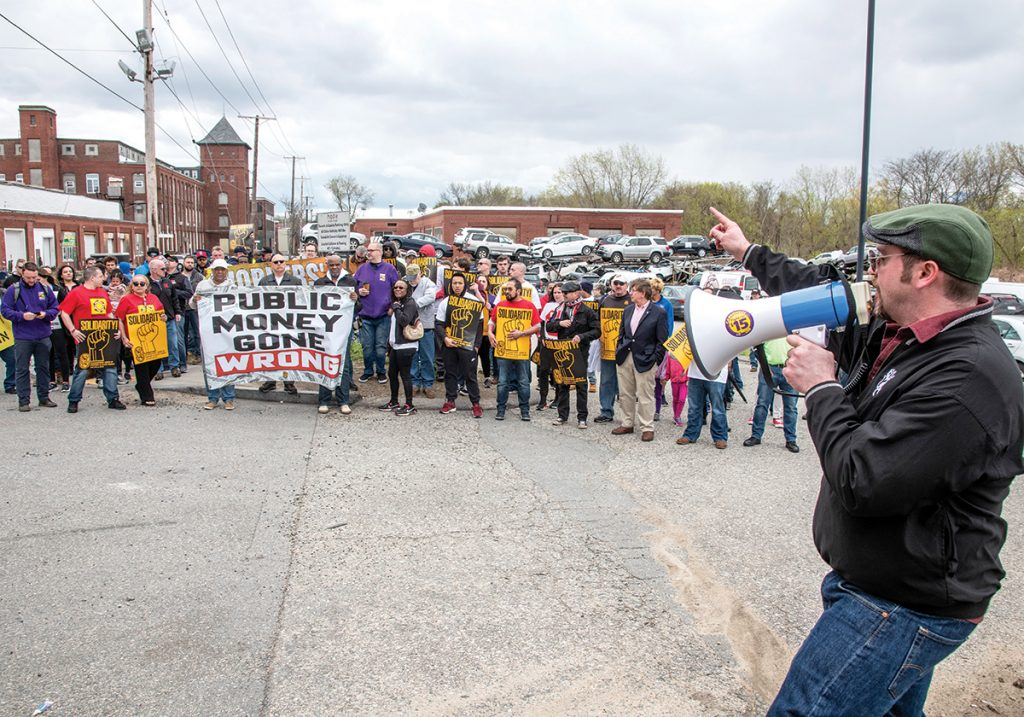 PROTEST: Justin Kelley, right foreground, union representative of the International Union of Painters and Allied Trades, leads a worker-safety rally to decry a workplace accident that injured three workers about a year ago at the Hope Artiste Village in Pawtucket. / PBN PHOTO/MICHAEL SALERNO