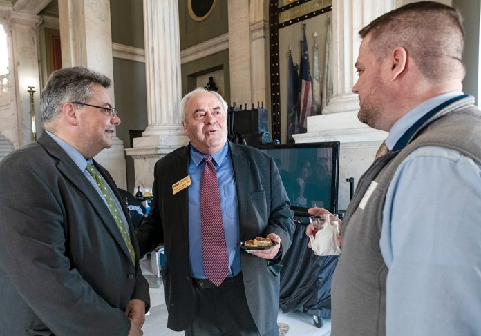 LEGISLATIVE RECEPTION: Lobbyist George Zainyeh, left, speaks with Northern Rhode Island Chamber of Commerce President and CEO John Gregory, center, and Robert Wheeler, owner of dog day care center Friends of Toto in Pawtucket, during the Rhode Island Chamber of Commerce Coalition's annual legislative reception at the Statehouse on March 26.  