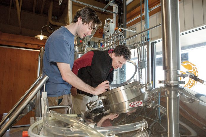 EXPANDED OPERATION: Newport Vineyards co-owner John Nunes, right, works on a batch of Vineyard Pilsner with Kevin Beachem of Taproot Brewing. The brewery was added to the vineyard as part of a $4 million renovation and expansion.
