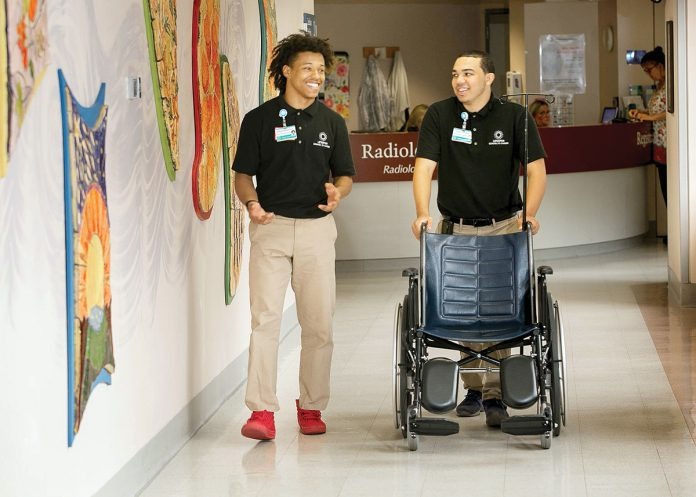 SMOOTH RIDE: Elijah Matthews, left, and Xavier Rivera work in central transport at Rhode Island Hospital in 2018. The job, often filled in the summer by interns, involves moving patients and equipment. / COURTESY LIFESPAN CORP.