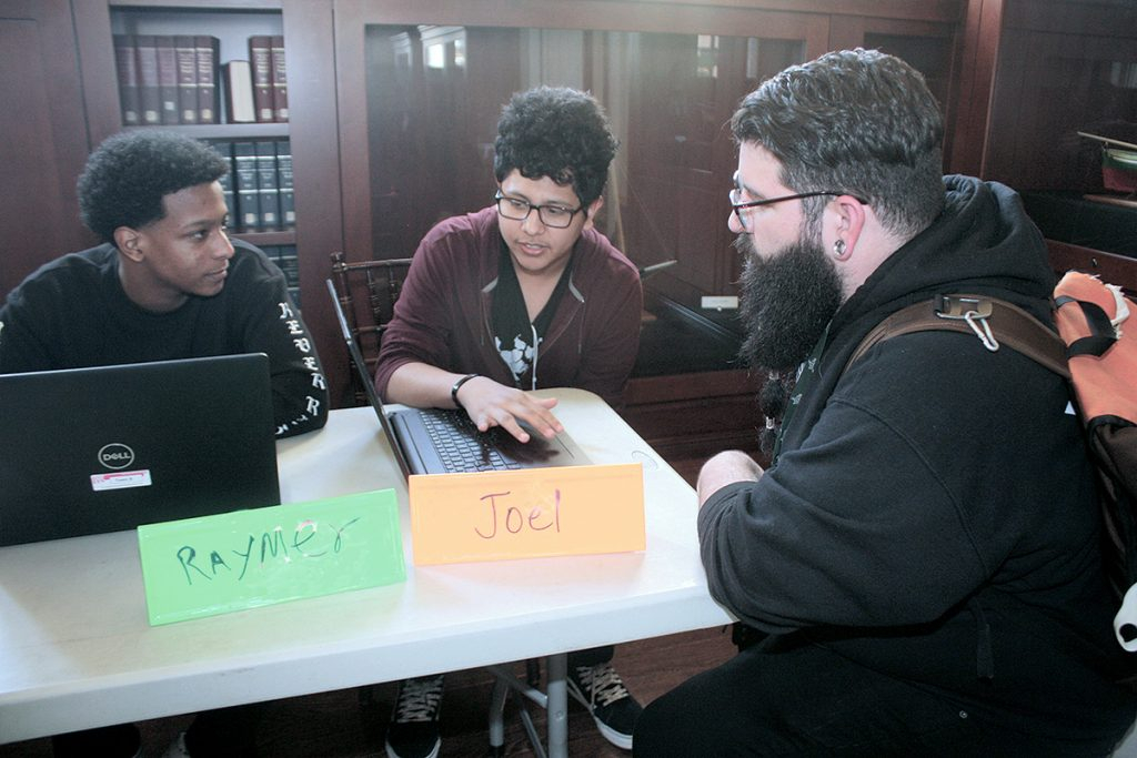 TEEN CODERS: From left, Raymer Peraota, 17, and Joel Monterroso, 16, both of Providence, discuss final assignments for Teen Rhode Coders, the library's free computer-programming course for youths, with Kevin Cordeiro, a Trinity Academy for the Performing Arts instructor. The event was held in May in the library's original wing, built in 1900.