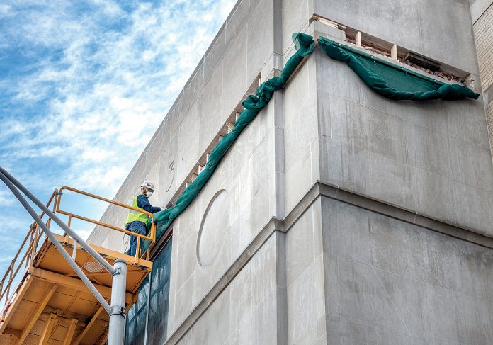 REHAB MASON Mike DeQuattro works on the deteriorated limestone strip at the top of the fascia of the Providence Public Library's Empire Street wing in May. The library has been awarded $750,000 by the Champlin Foundation for the ongoing construction work. / PBN FILE PHOTO/MICHAEL SALERNO