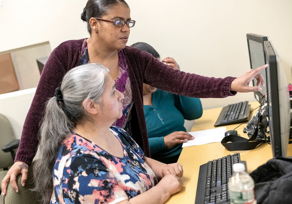 IN SESSION: Residents of Providence's Olneyville neighborhood participate in on-site classes run by the library in cooperation with the Providence Housing Authority. Maria Quinonez, foreground, works with instructor Betty Tavares.
