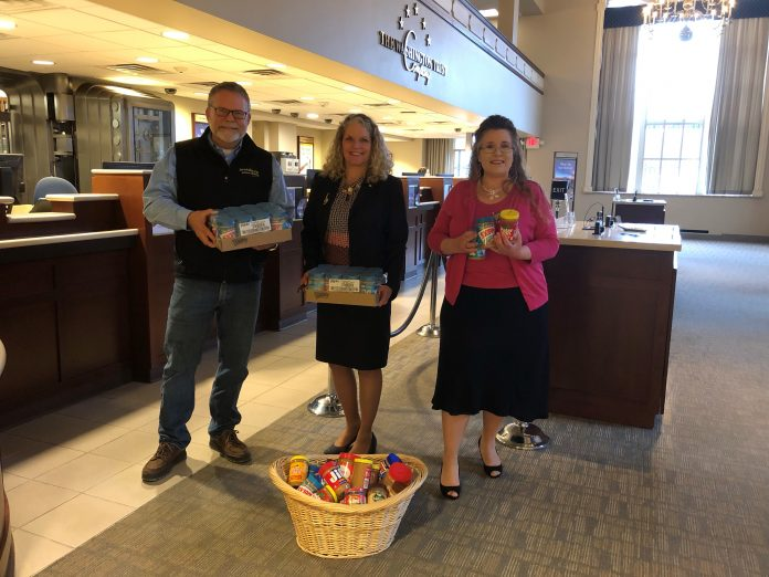 FROM LEFT TO RIGHT, PHIL MASON of ServiceMaster by Mason; Elizabeth Eckel, chief marketing officer for The Washington Trust Co.; and Beth Markowski-Roop of ServiceMaster by Mason pose with donated peanut butter at Washington Trust's Westerly Branch as ServiceMaster by Mason delivers boxes of peanut butter to Washington Trust's 19th annual Peanut Butter Drive. / COURTESY THE WASHINGTON TRUST CO.