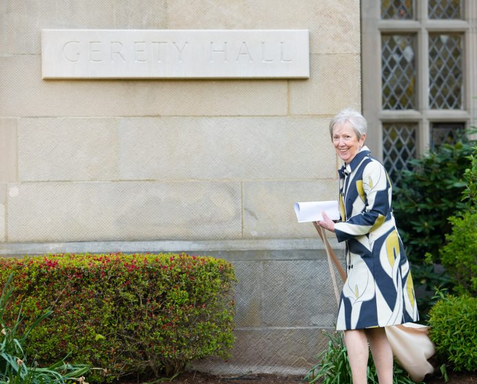 SISTER JANE GERETY unveils the nameplate on the exterior of the building at Salve Regina University in Newport that was dedicated in her name on Thursday. Gerety is retiring after serving 10 years as Salve Regina's president. /ANDREA HANSEN/COURTESY SALVE REGINA UNIVERSITY
