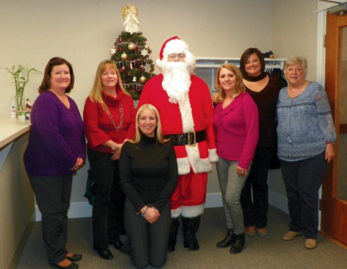 IN THE SPIRIT: Members of the Carey, Richmond & Viking staff mark the holidays with a visit from Santa.