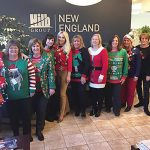 MODEL EMPLOYEES: Staff members at The Hilb Group of New England show off their gaudy holiday sweaters.