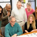 COLLABORATIVE TASK: Staff members from several R.I. Housing departments review plans for a housing development.  / COURTESY R.I. HOUSING AND MORTGAGE FINANCE CORP.