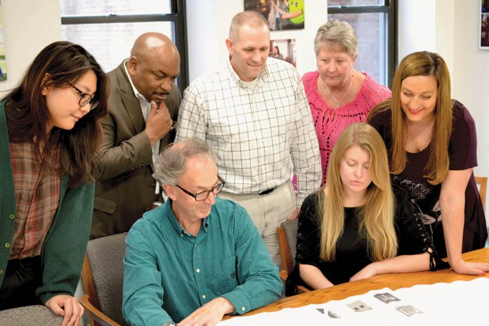 COLLABORATIVE TASK: Staff members from several R.I. Housing departments review plans for a housing development. 