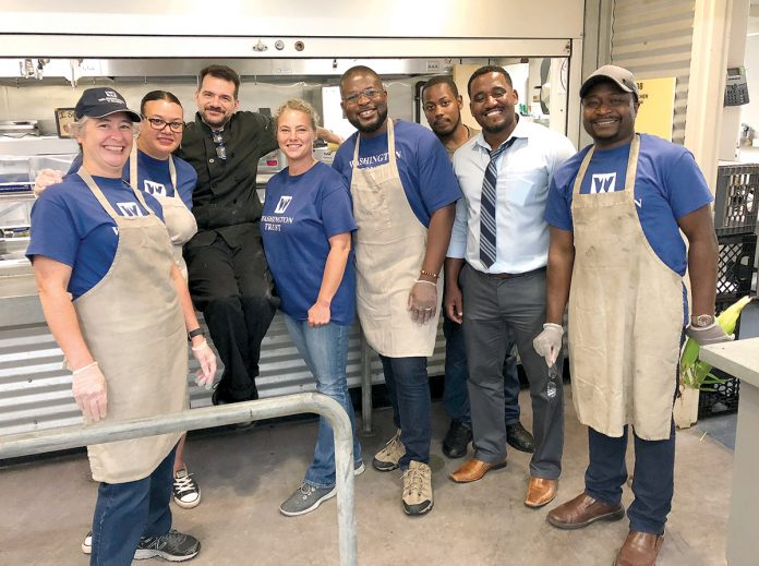 PREPPED TO HELP: Washington Trust employees volunteer to serve meals to the community at the McAuley House in Providence. / COURTESY THE WASHINGTON TRUST CO.