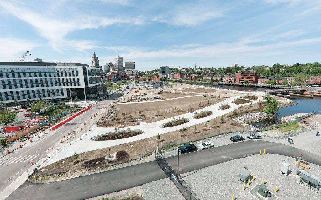SLOW BUT SURE: The Wexford Science & Technology innovation center, left, and the public park, center, being built on the former I-195 land in Providence, are early pieces of the creation of a new neighborhood in the heart of Providence. / PBN PHOTO/ARTISTIC IMAGES