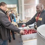 BUSY KITCHEN: Kevin Burton, right, a staffer in the Amos House soup kitchen in Providence, offers an apple to Kashaka Williams of Providence. Amos House President and CEO Eileen Hayes said the soup kitchen is the largest in the state and serves between 120,000 and 130,000 meals annually. / PBN PHOTO/MICHAEL SALERNO