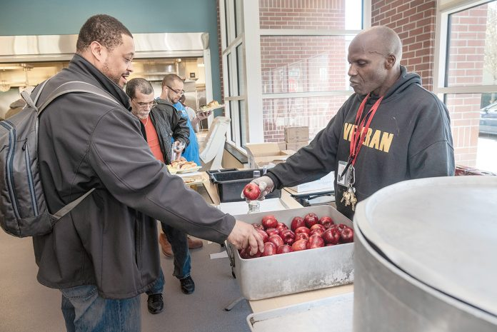 BUSY KITCHEN: Kevin Burton, right, a staffer in the Amos House soup kitchen in Providence, offers an apple to Kashaka Williams of Providence. Amos House President and CEO Eileen Hayes said the soup kitchen is the largest in the state and serves between 120,000 and 130,000 meals annually.