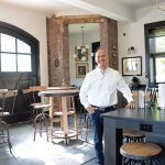 ANTIQUE FIREHOUSE: Christopher Bicho, owner of six boutique hotel properties in Newport, including the Town & Tide Inn, stands in a renovated, antique firehouse that he rents out as an Airbnb site.