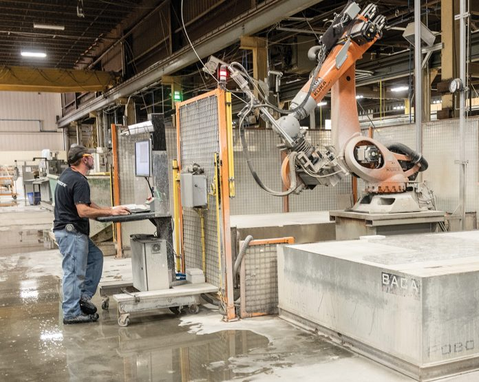 PRECISE CUTS: Bert Lima, shop supervisor at The Beck Cos., operates the robotic saw jet from BACA Systems. It allows precise cuts and details in the stone countertops and pieces that Beck manufactures. / PBN PHOTO/MICHAEL SALERNO