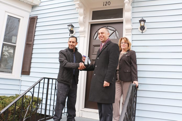 RENOVATED HOME: Homeowner Carlos Reyes, left, is pictured with Providence Mayor Jorge O. Elorza and Smith Hill Community Development Corp. Executive Director Jean Lamb in front of his home at 120 Camden Ave. during ceremonies to celebrate homeowners moving into houses renovated under the city's EveryHome program.