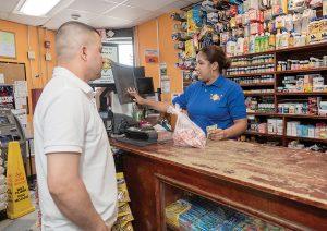 "WORK HARDER: Mi Quisqueya Super Market Manager Luisa Goris helps customer Elias Ramirez at the shop on Broad Street in Providence. Goris said the city could ""work harder"" to address neighborhood problems. / PBN PHOTO/MICHAEL SALERNO"