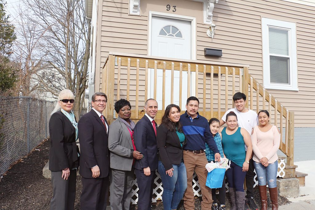 NEW DWELLING: The Morente family stands with city officials in front of the home they bought at 93 Superior St. in Providence that was renovated through the city's EveryHome program. From left: Jeri Martins, home ownership manager, West Elmwood Housing Development Corp.; receivership attorney Stephen Del Sesto, Pierce Atwood LLP; City Councilwoman Mary Kay Harris; Mayor Jorge O. Elorza; Teresa Guaba, group facilitator, Neighbors 4 Revitalization; and homeowner Juan Morente, with his daughter, Kiara, 11; his wife, Paula; his son, Kevin, 15; and his daughter, Datsaris, 17. / COURTESY CITY OF PROVIDENCE