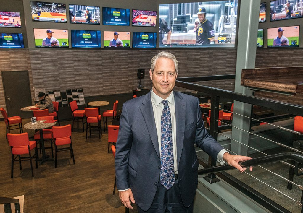 POPULAR BET: Marc Crisafulli, president of Rhode Island operations for Twin River Worldwide Holdings, stands in the newly opened sportsbook at Twin River Casino Hotel in Lincoln. He said the NFL has been the most popular so far for sports betting. In February, the two casinos in Rhode Island lost $890,623 when payouts were made to Super Bowl bettors who placed bets on the New England Patriots. / PBN PHOTO/MICHAEL SALERNO