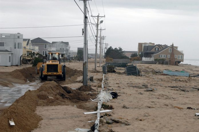 OVER 25,000 single-family homes are considered at-risk to be impacted by storm surge in the event of a Category 4 hurricane in Rhode Island. Above, a machine clears sand off Atlantic Avenue in Westerly after the remnants of Hurricane Sandy battered Rhode Island's coast in 2012. / PBN FILE PHOTO/BRIAN MCDONALD