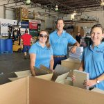 PACK IT UP: Bridge Technical Talent staff members help fill and distribute backpacks for children at the nonprofit Back to School Celebration. / COURTESY BRIDGE TECHNICAL TALENT