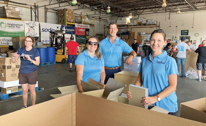 PACK IT UP: Bridge Technical Talent staff members help fill and distribute backpacks for children at the nonprofit Back to School Celebration.