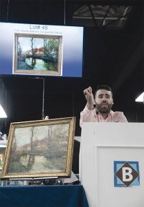 IMPRESSIONIST PAINTING: Auctioneer and Pop-culture Director Travis Landry takes bids on a reflective impressionist painting by Fritz Thaulow during an auction at the Bruneau & Co. Auctioneers gallery in Cranston. The painting sold for $7,000. / PBN PHOTO/MICHAEL SALERNO