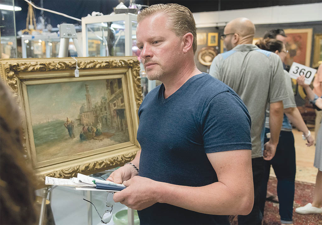 PLACING BIDS: Coventry resident Walter Sroka looks to place some bids on auction items at the Bruneau & Co. Auctioneers gallery in Cranston. / PBN PHOTO/MICHAEL SALERNO