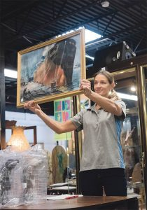 """GOING ONCE: Gallery assistant Heidi Kirchner holds up """"Industrial Tanker,"""" a painting by Spencer Crooks, for bids during an auction at Bruneau & Co. Auctioneers in Cranston. / PBN PHOTO/MICHAEL SALERNO"""