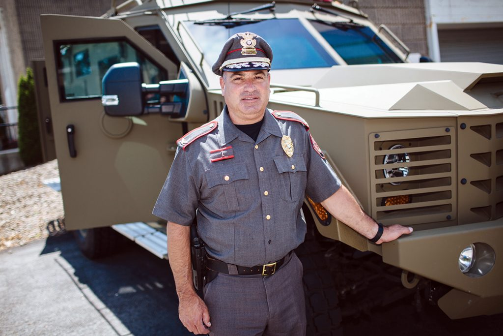 """GOOGLE SETTLEMENT: East Providence Chief of Police William Nebus stands in front of an armored SWAT truck the department purchased for $400,000 using money it received as part of a 2012 settlement with Google Inc. An investigation found Google allowed Canadian pharmacies that illegally imported drugs into the United States to advertise on its """"Adwords"""" platform. / PBN PHOTO/RUPERT WHITELEY"""