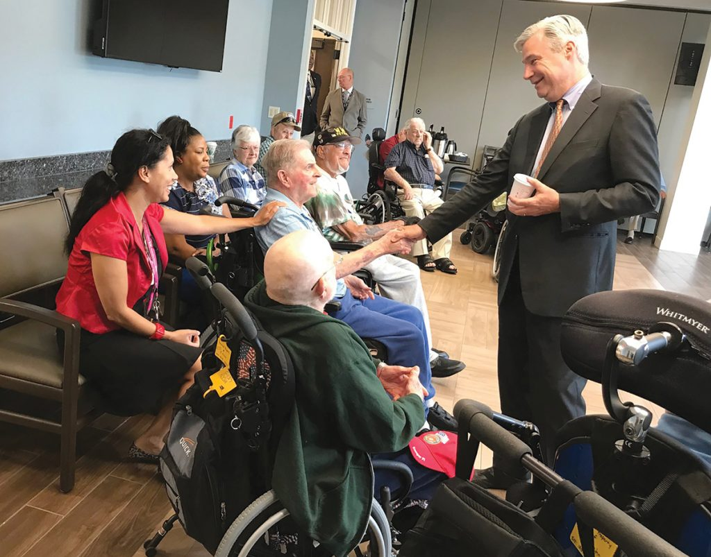 """LEAD LAWSUIT: Sen. Sheldon Whitehouse, D-R.I., visits members of the Rhode Island Veterans Home in Bristol last summer. In 1999, when Whitehouse served as R.I. attorney general, he filed a lawsuit against lead paint makers, alleging the paint companies marketed and sold lead-based paint with """"full knowledge"""" that it was toxic. / COURTESY OFFICE OF SHELDON WHITEHOUSE"""