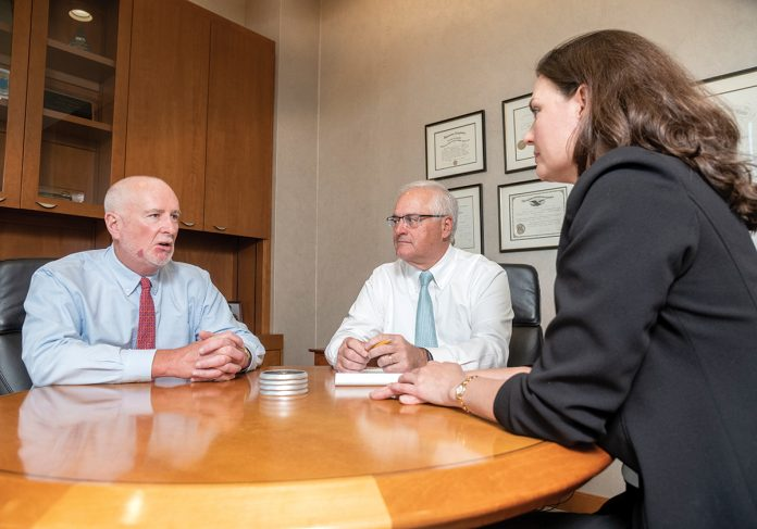 MAJORITY MARKET: Brian J. Spero, center, CEO and president of The Beacon Mutual Insurance Co., speaks with Michael Lynch, vice president of legal services, and Amy Vitale, vice president, general counsel and assistant secretary. Spero said his company has 60% of the workers' compensation market for Rhode Island. / PBN PHOTO/MICHAEL SALERNO