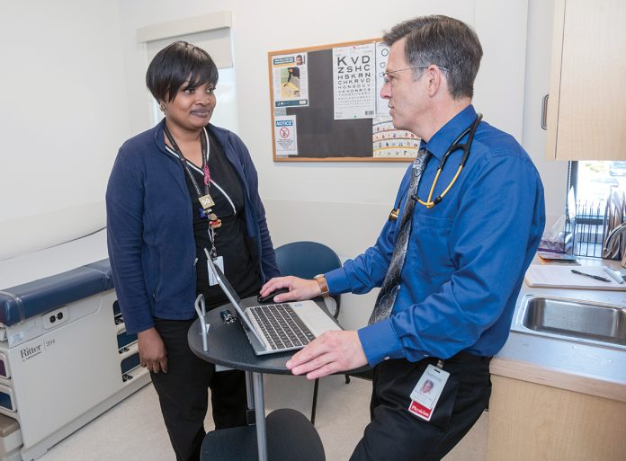 CLOSE COORDINATION: Dr. David Bourassa, right, chief medical officer for Thundermist Health Center, speaks with medical assistant Aminata Gassama. Bourassa said primary care doctors can coordinate a patient's care better than a CVS MinuteClinic because they know a patient's medical history. / PBN PHOTO/MICHAEL SALERNO