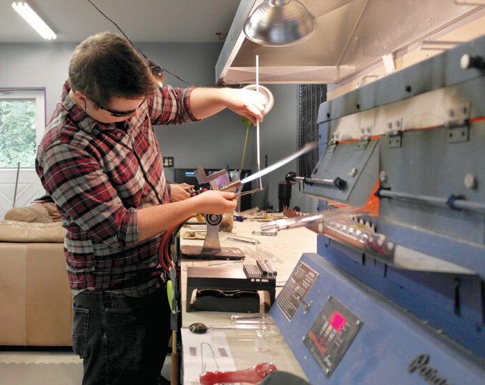 GLASSWORK: Ben Kurose, owner of Greenwich Bay Glass, pulls a gather, or hot ball of glass, to stretch it into a stringer, or thin rod of glass, which is used to apply small detail work.