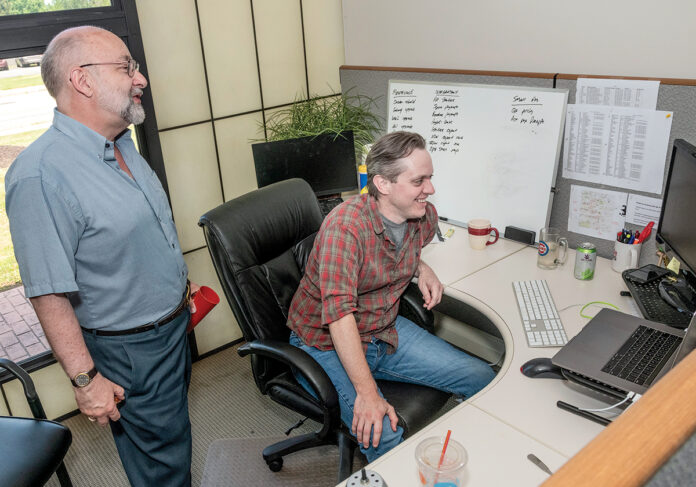 """SHELL GAME: Bill Ostendorf, left, Creative Circle Media Solutions president and founder, with programmer Tim Benson. A former editor at The Providence Journal, Ostendorf says recurring layoffs have left the paper """"a shell of what it used to be."""" / PBN PHOTO/MICHAEL SALERNO"""