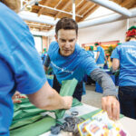 FUN, YES, BUT MUCH MORE: Hasbro CEO and Chairman Brian Goldner takes part in a 2016 companywide effort to pack toys for children and families, part of the company's ongoing philanthropic efforts and one which its decision to cut back on plastic packaging is consistent with.  / PBN FILE PHOTO/ RUPERT WHITELEY