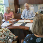 RETIREMENT OPTIONS: Glenn King, FM Global's manager of employee benefits, meets with staff. From left, foreground, are Tricia Fay, North America benefits manager, and Jill Goodman, retirement plans manager. From left, background, are Carole Williamson, manager health and welfare plans, and King. FM Global offers both a 401(k) plan and a pension plan to its employees.