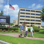 INCREASED WORKFORCE: From left, Justin Monte, Suzanne Violet and Kate Arsenault walk along the Naval Undersea Warfare Center Division Newport campus. The workforce at the 180-acre, 76-building complex mainly consists of highly paid professionals such as engineers and scientists, administrators and technicians. The workforce has grown by more than 200 employees to between 6,100 and 6,200 since last fall, 4,500 of whom live in Rhode Island.