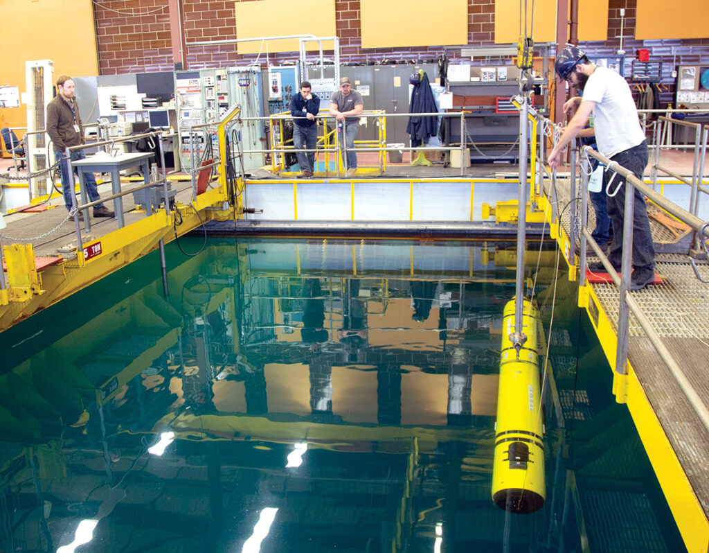 TESTING POOL: Naval Undersea Warfare Center Division Newport employees submerge an unmanned underwater vehicle in a testing pool at the facility.