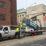 POYANT, BASED IN New Bedford, has acquired Dion Signs of Central Falls. Above, Dion Signs installing a sign for Roger Williams University. / COURTESY POYANT