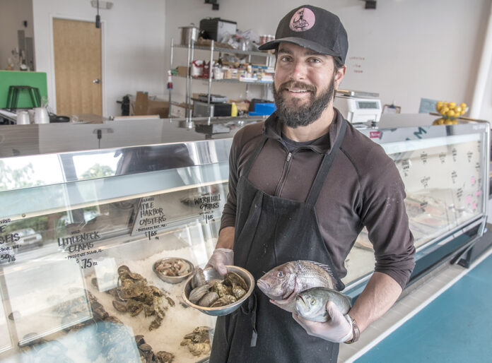 FRESH VARIETY: Stu Meltzer, owner of Fearless Fish Market in Providence, shows off Watch Hill oysters, quahogs, a scup and a bluefish. 
