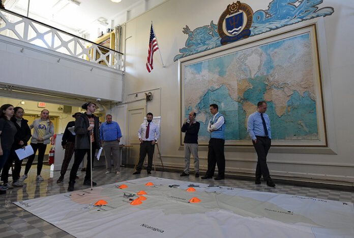 U.S. NAVAL WAR College faculty members along with students from the Massachusetts Institute of Technology participate in a humanitarian response and disaster relief aid simulation during the MIT students' visit to NWC's Sims Hall. / COURTESY U.S. NAVY/MASS COMMUNICATION SPECIALIST 2ND CLASS JESS LEWIS